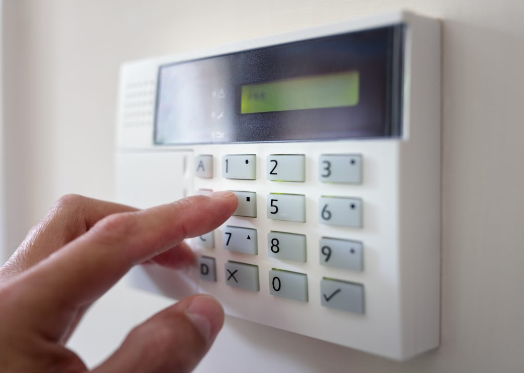 man entering password on alarm system
